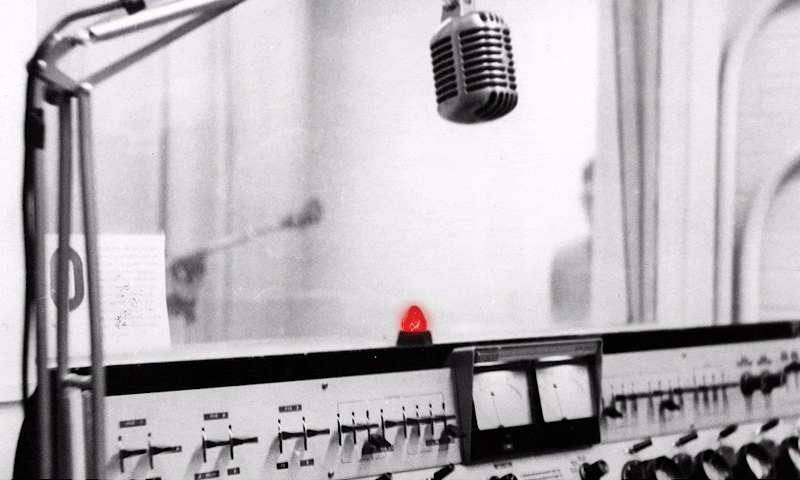 black and white image of a radio studio, with a red LIVE light