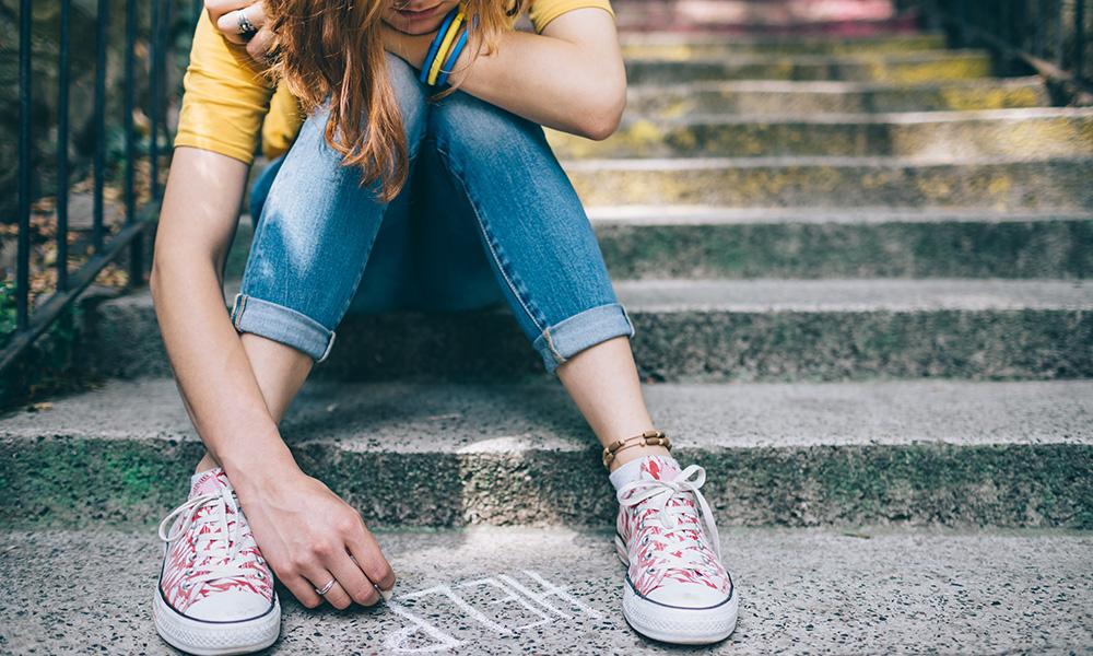 teenage girl writes the word HELP in chalk in the sidewalk near her feet