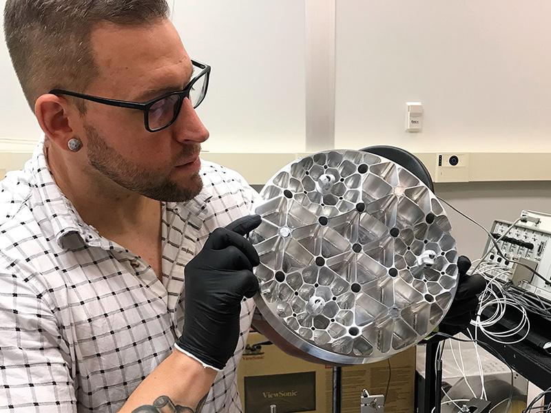 Nick Hovath holding a telescope array