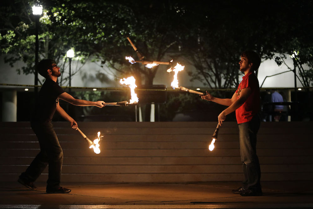 two students juggle fire