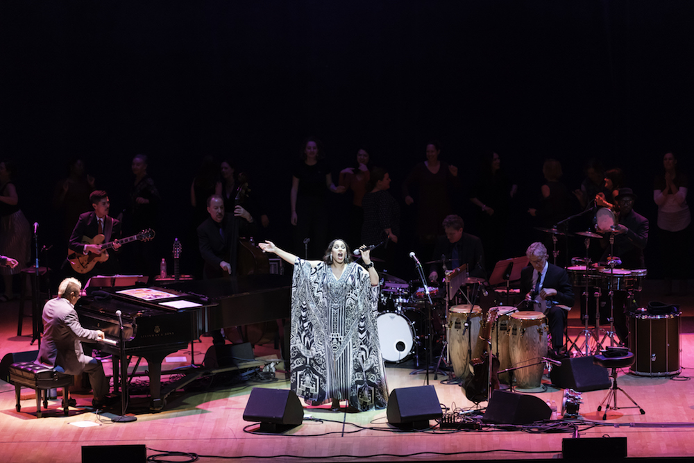woman sings on stage surrounded by musicians