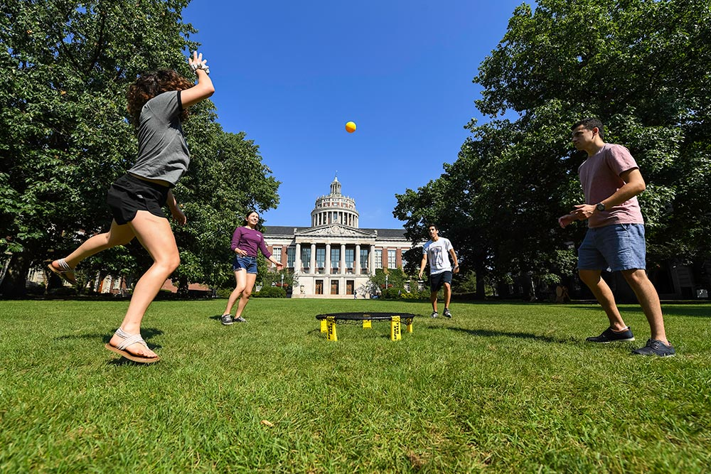 four students playing a game of spikeball -- hitting a yellow ball into a small round net on the ground -- with Rush Rhees Library in the background