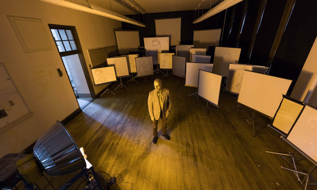 art professor stands in a disused classroom that has been filled with old-fashioned fimlstrip screens, each showing an image from an old high school yearbook