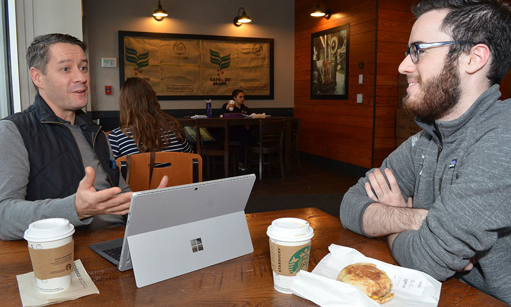 two people sit and talk at a table in a coffee shop, a laptop on the table in front of them