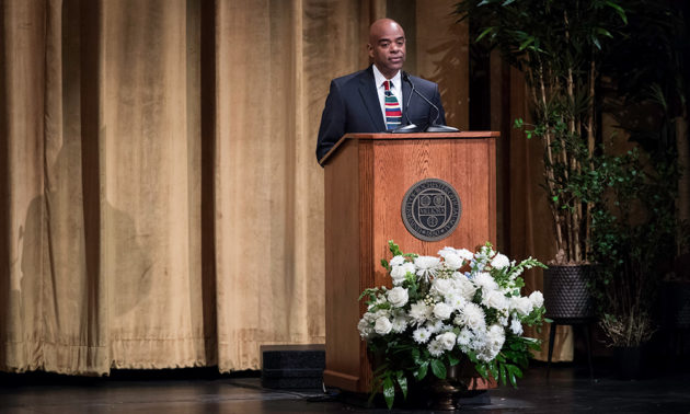 Lee Koonce speaking from a podium on stage at Strong Auditorium