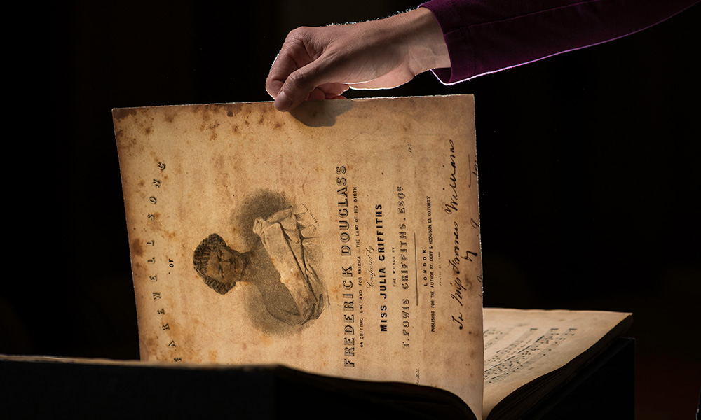 hand holding a piece of sheet music bearing the image and name of Frederick Douglass