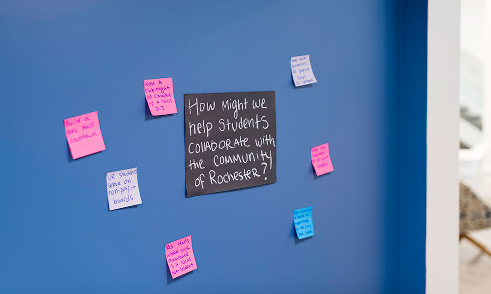 a blackboard filled with colorful post-it notes, the largest one in the center reads HOW MAY WE HELP STUDENT COLLABORATE WITH THE COMMUNITY OF ROCHESTER