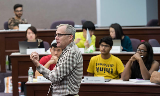 professor in front of students in a lecture hall in the Simon Business School. One wears a t-shirt that reads THINK DIFFERENT printed upside down