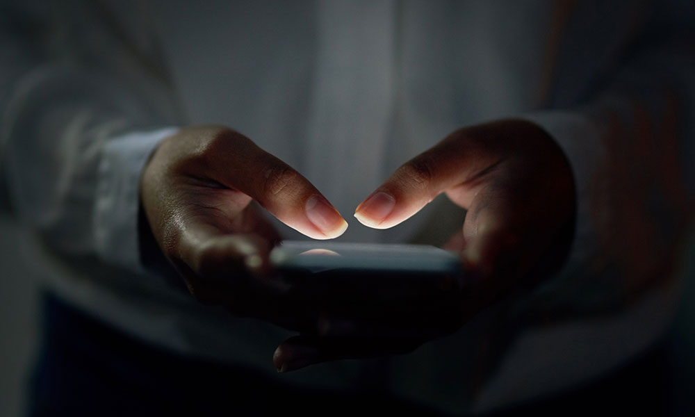 two hands using a smartphone lit with a dim light from the screen