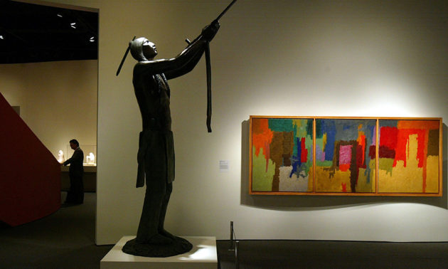 sculpture of an American Indian stands next to an abstract painting in an exhibit at the Smithsonian's National Museum of the American Indian