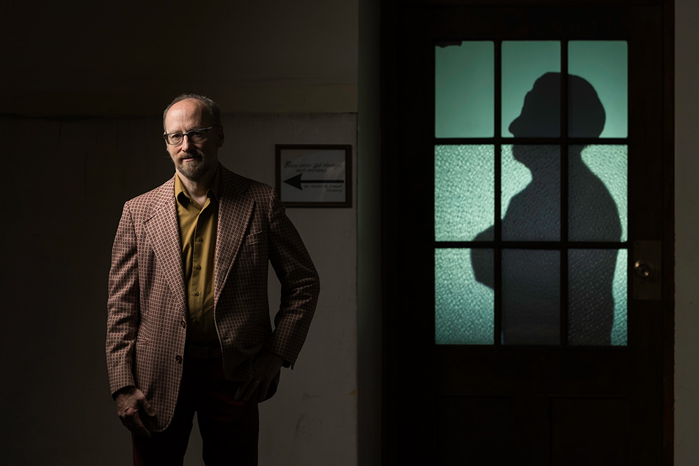 artist Allen Topolski stands next to a classroom door, lit from behind and showing the silhouette of a person