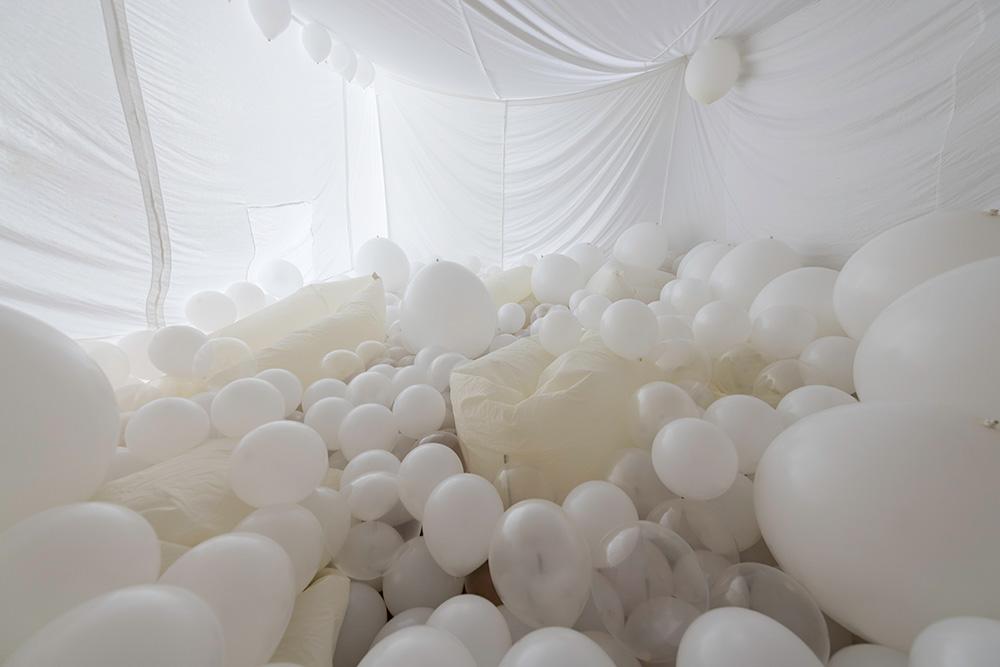 a white room completely full of white balloons