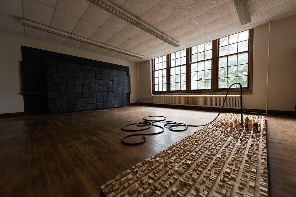 a large room with a wooden floor, and on the floor are wooden blocks the appear to form a cityscape or skyline