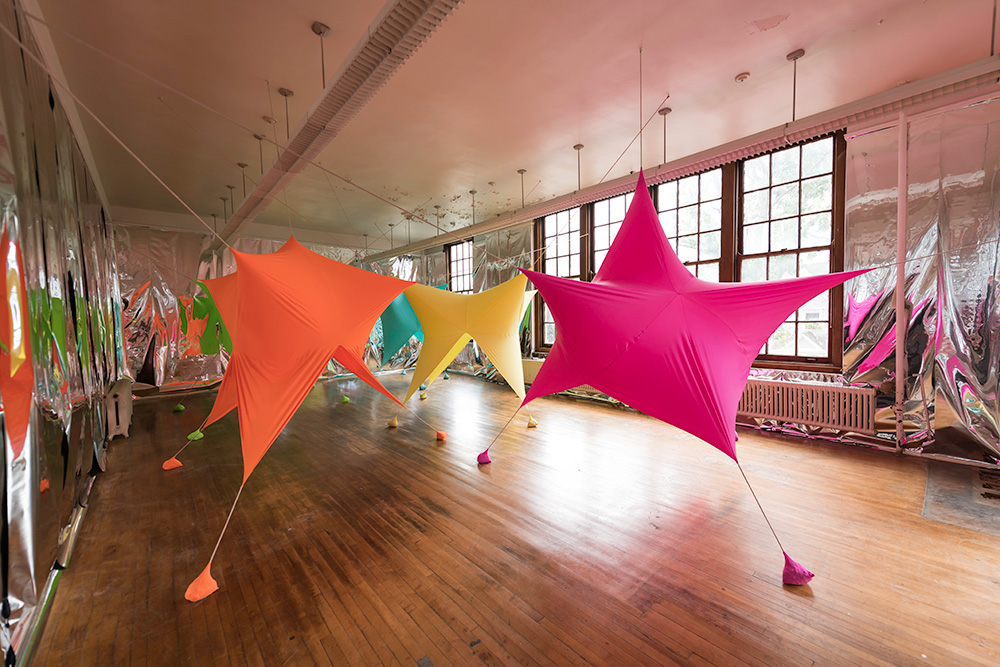 large room filled with colorful, star shaped balloons