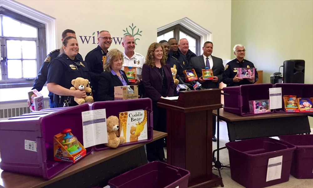 DPS officers with other local law enforcement teams stand with purple boxes and donated gifts for the Willow Domestic Violence Centeromestic Violence Center