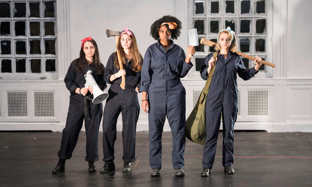 four women in work jumpsuits with a megaphone, an axe, a cleaver and a bat
