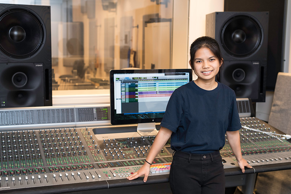 student stands in front of a large sound board