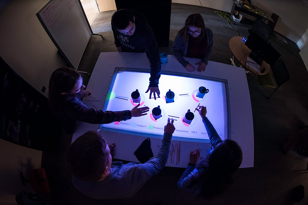 overhead shot of a lighted table with hands reaching out over it to move mugs across it.