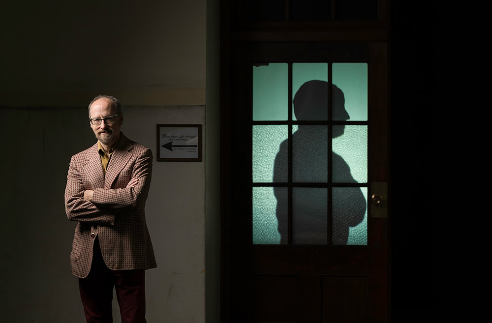 Alan Topolski stands with his arms crossed, and a silhoutte with its arms crossed is projected onto a classroom door next to him.
