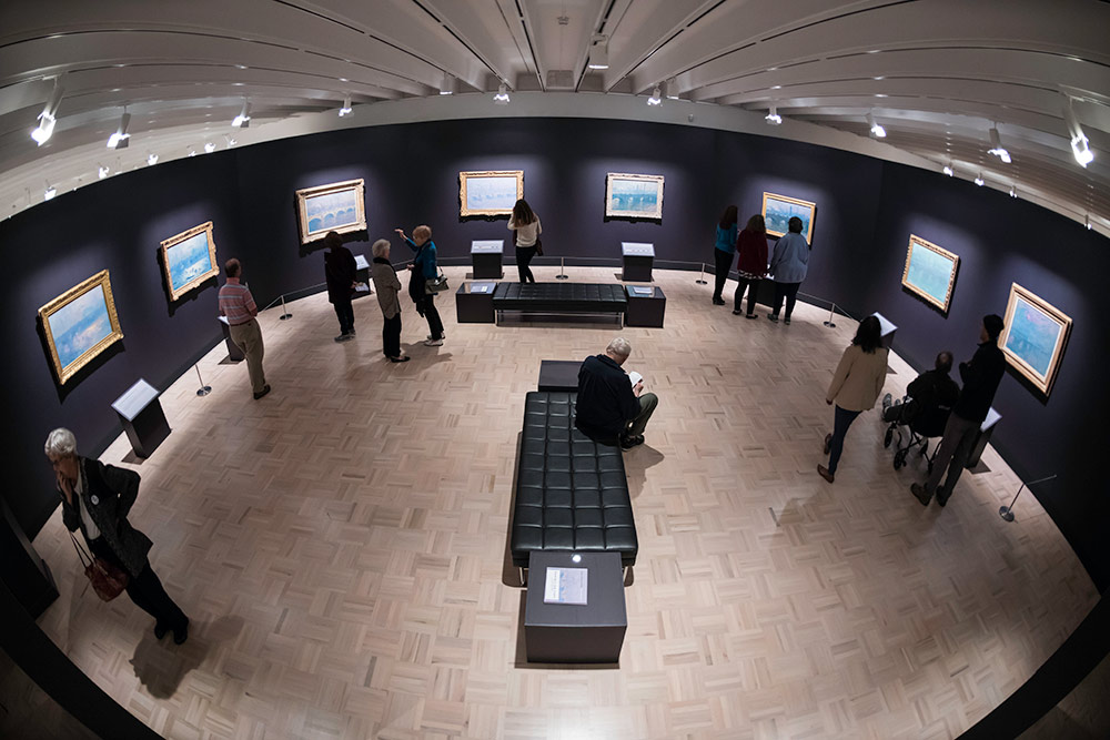 fish-eye lens view of an art exhibition with eight Monet paintings on the walls of a museum.