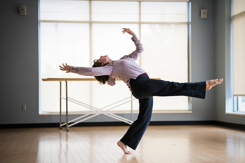 Missy Pfohl-Smith in a dance studio, leaning back and reaching over her head.