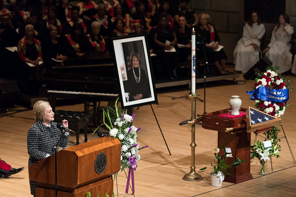 Hillary Clinton on stage at a funeral service with flowers and a portrait of Louise Slaughter.