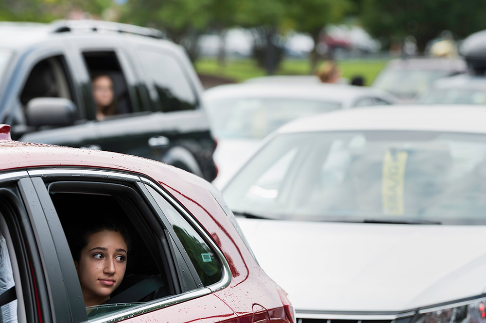 student looks out the window of a car, with a line of cars behind her.