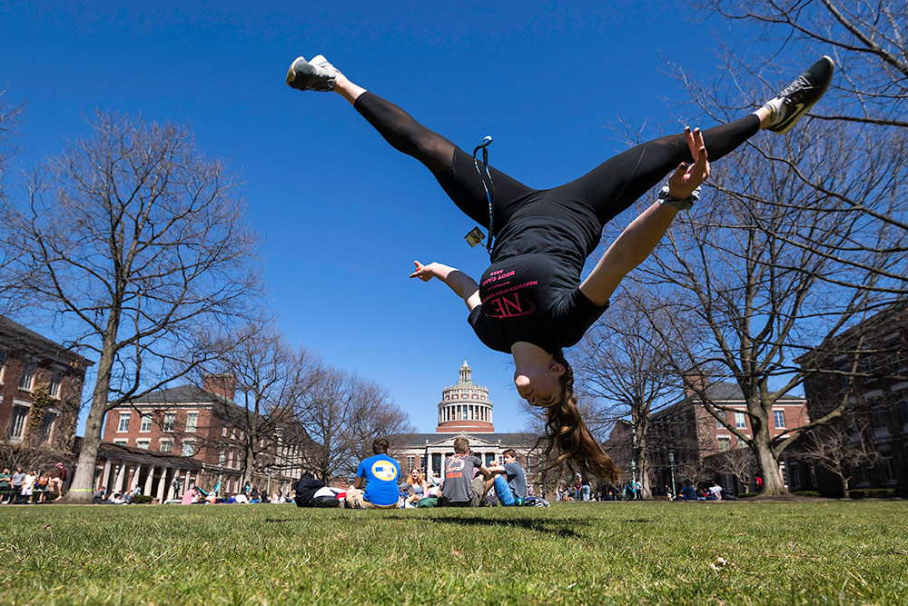 student appears suspended upside down in mid air, with the library tower in the background.
