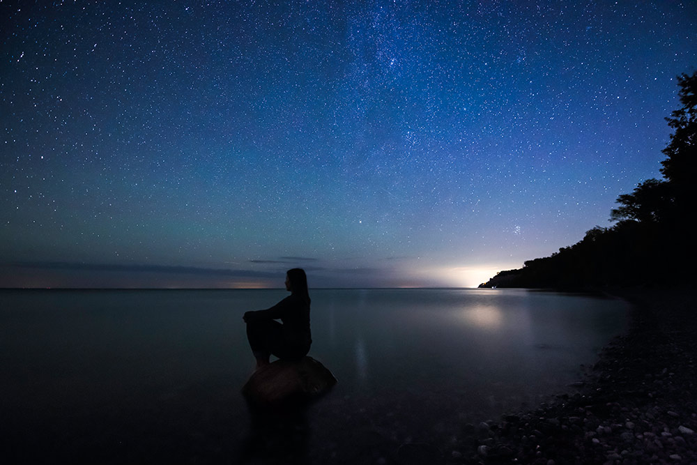 nighttime image of a person kneeling on a beach, with the lake and a sky full of stars in the background.