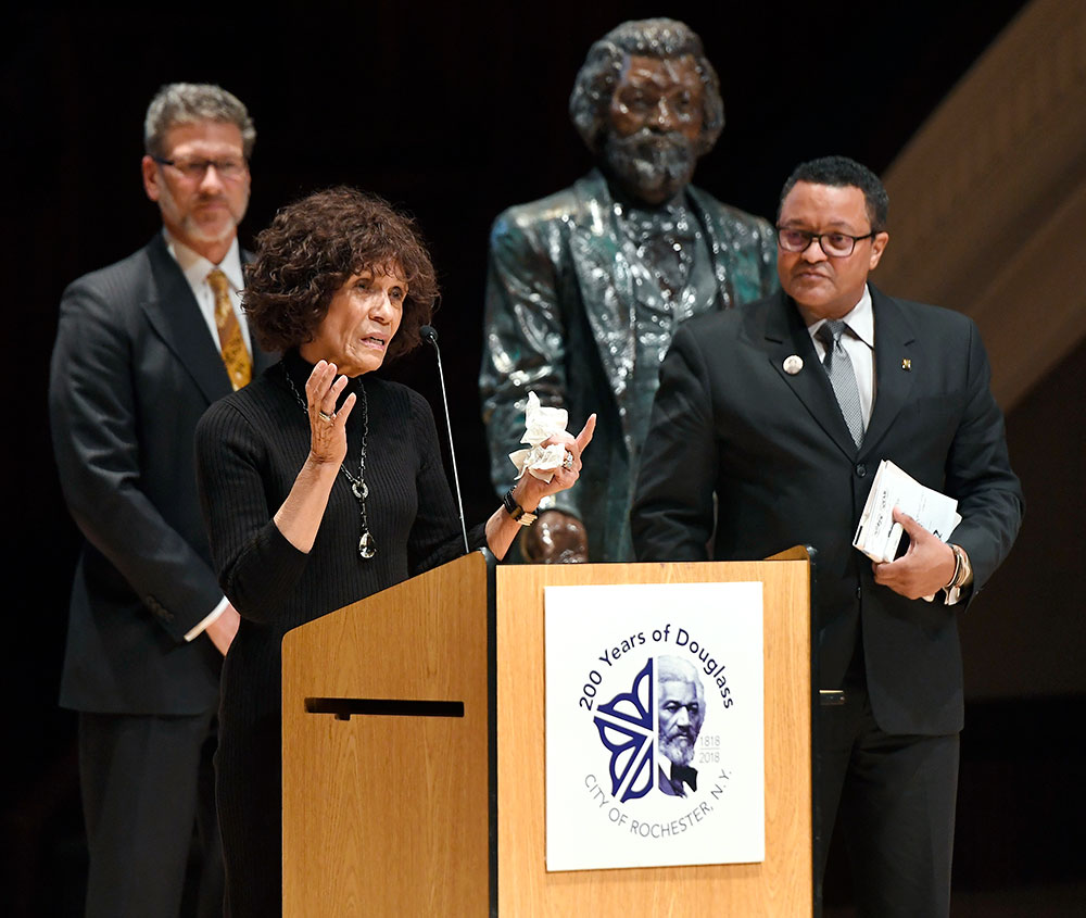 three people standing on stage, one behind a podium speaking, with a statue of Frederick Douglass in the background