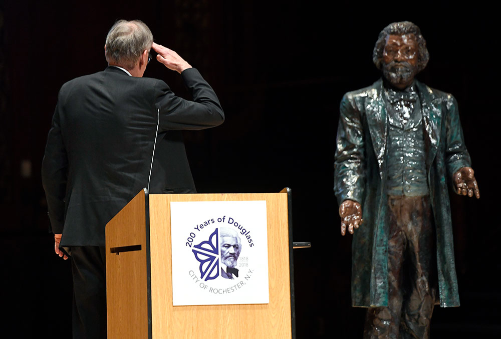 David Blight sands behind podium, turning to salute a statue of Frederick Douglass behind him.