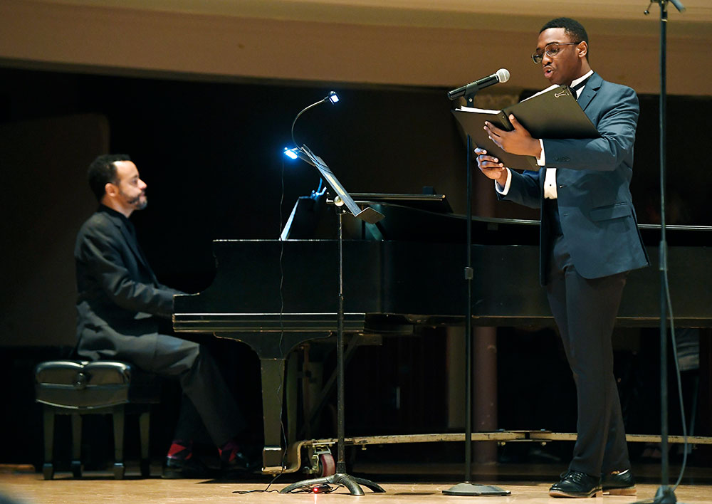 two musicians on stage, one playing the piano the other singing and holding a book of music