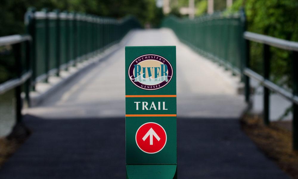 River bike trail sign leading over a bridge near the University of Rochester