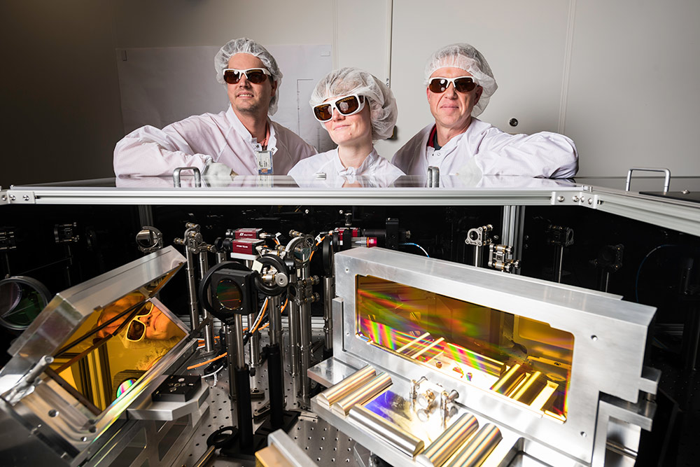 three scientists in clean suits and laser goggles stand in front of an array of optical devices