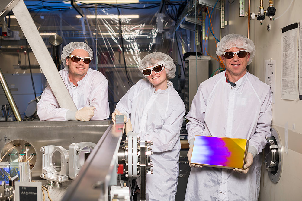 three researchers in clean suits and goggles, the one in the center holding a small, square prism-like device, and the one on the right holding a much larger version of the same device