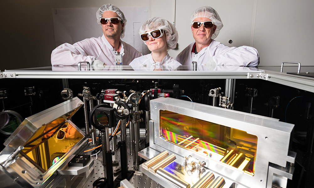 three researchers wearing laser goggles and clean suits stand over an array of optical devices