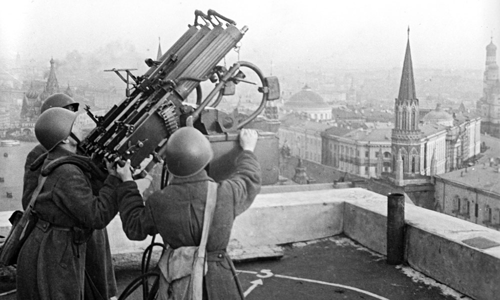 historical image of world war II soldiers operating a large gun on top of a building with the Moscow skyline in the background.