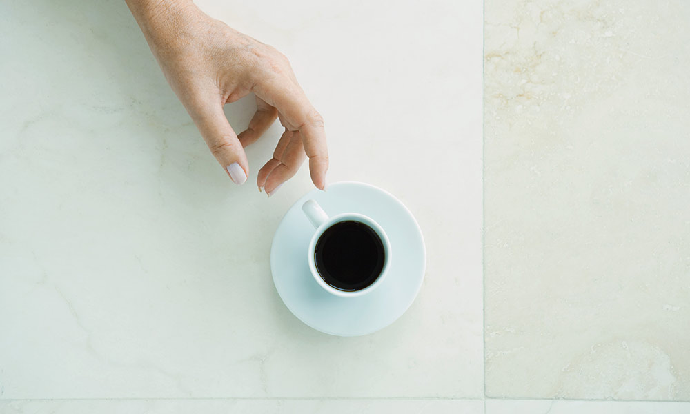 A hand reaches for a coffee cup.