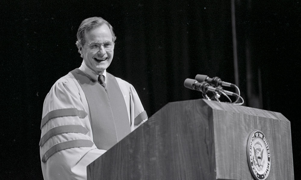 black and white photo of George H. W. Bush in academic attire standing behind a podium