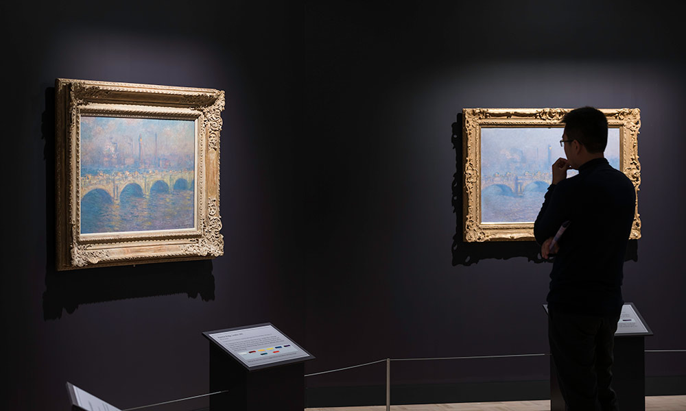 a person in shadow looks at two different Monet paintings, beautifully lit and showcasing different color variations of the same scene.