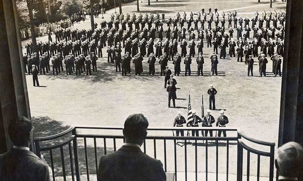 historical photo of three men on the balcony of Rush Rhees Library looking out over a large assembly of men in uniform on the quad