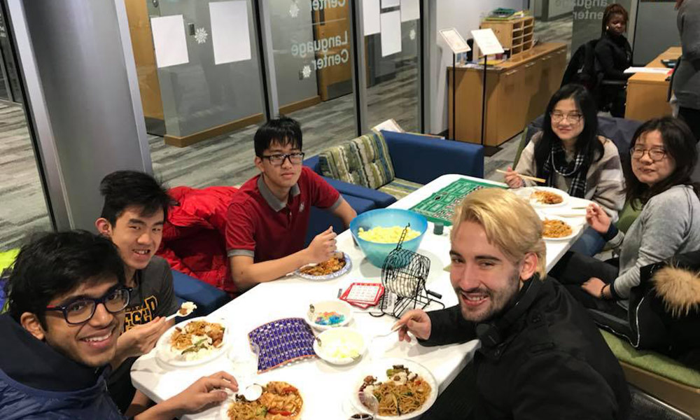 group of students at a table eating food and playing games