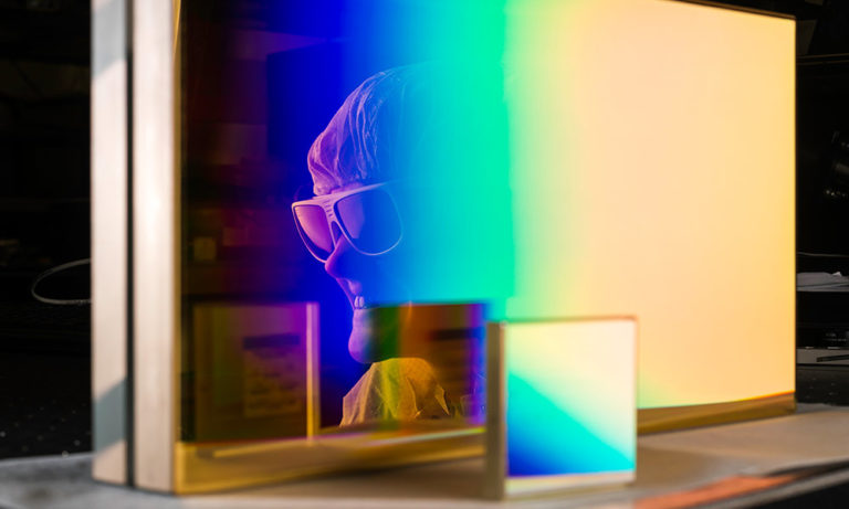 womans face wearing laser goggles and reflected in the glass of a rectangular prism