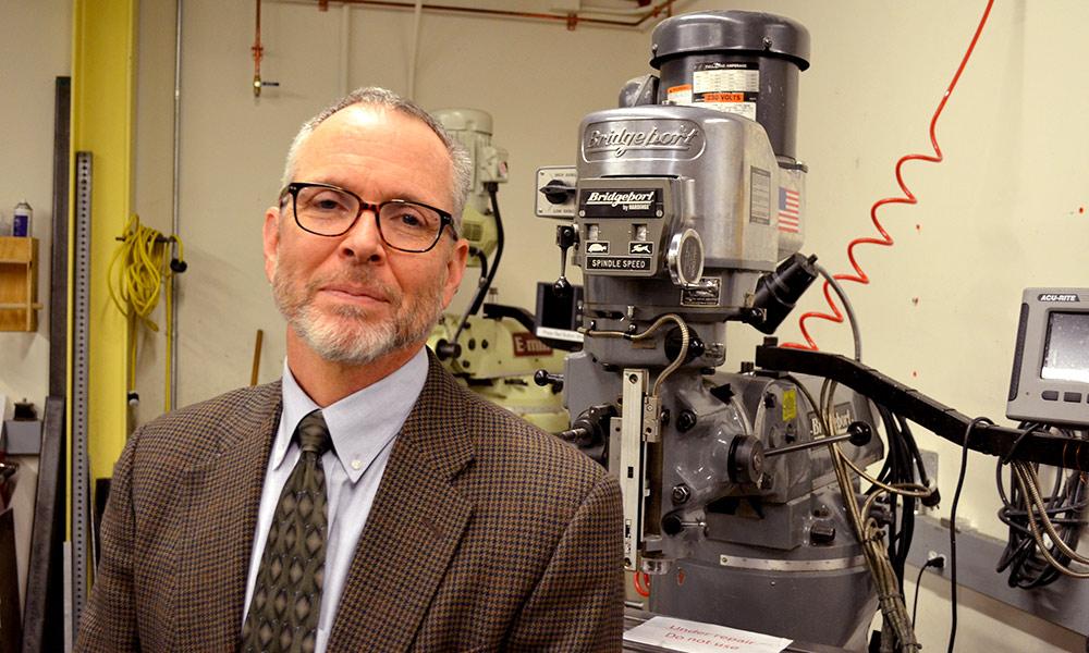 Jim Zavislan stands in front of a optics grinder in Rettner Hall.