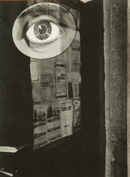 photo of a door covered in newsprint with a large illustration of a human eye.