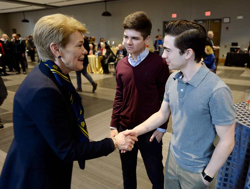 Sarah Mangesldorf shaking hands with students