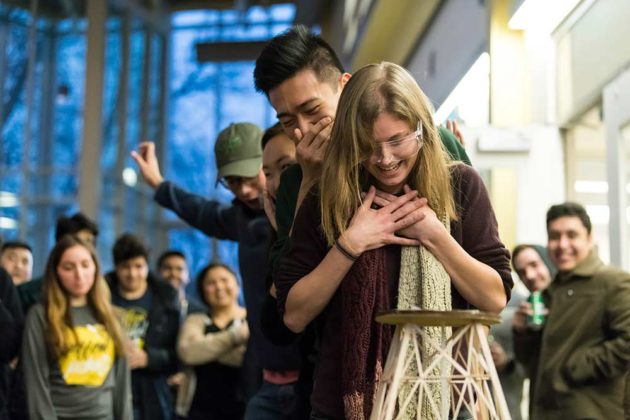 students gasp and hold their hands over the faces while looking at a fragile tower made of balsa wood slats in the foreground.