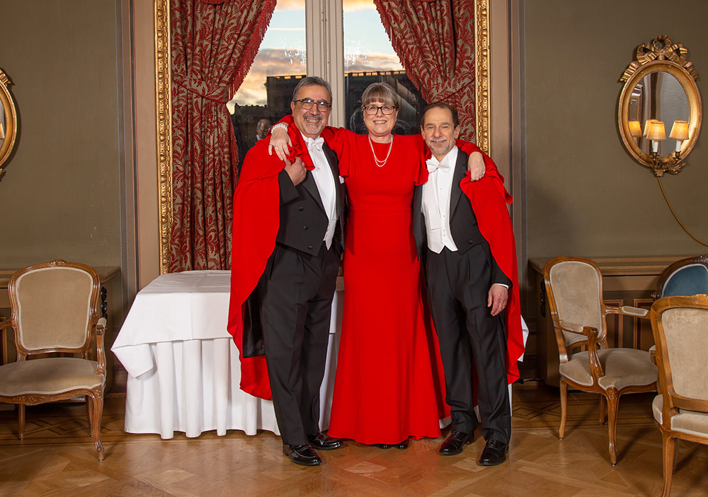 three people in formal attire, two in white tie and one in a red gown, smile and pose for a photo.
