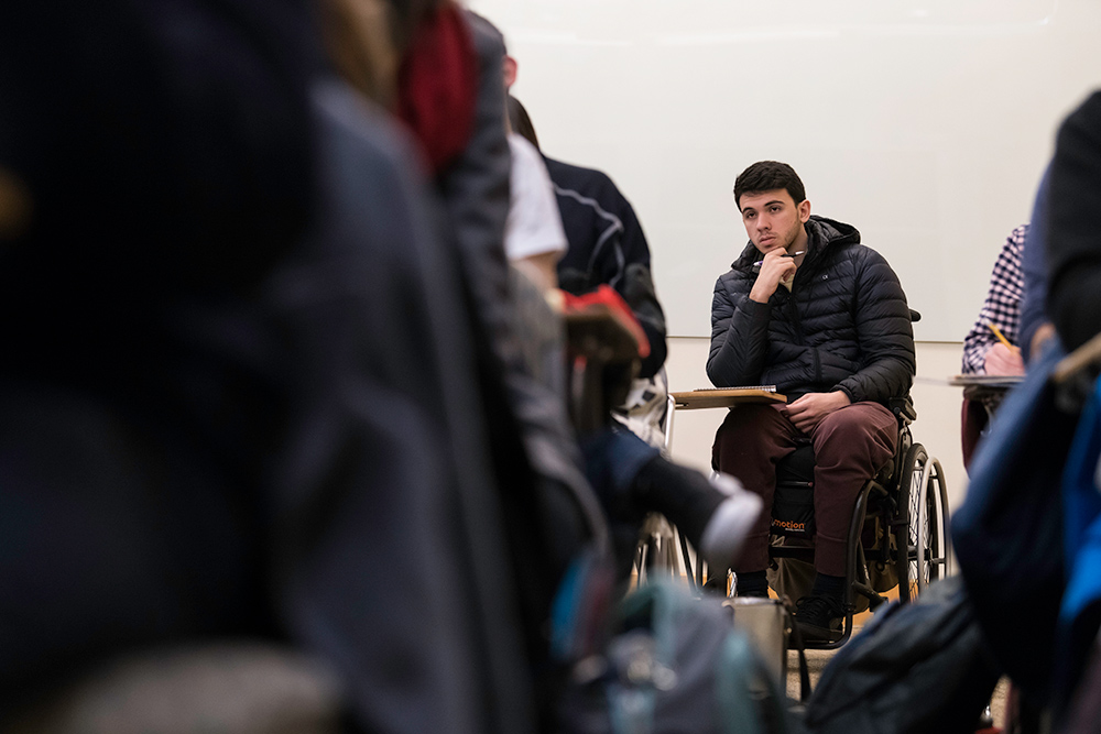 Giuliano Agostinho de Castro sitting in a classroom full of fellow students
