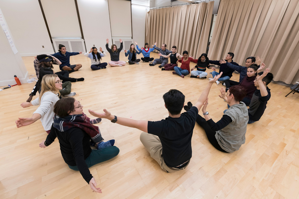 circle of students sitting on the floor of a dance studio